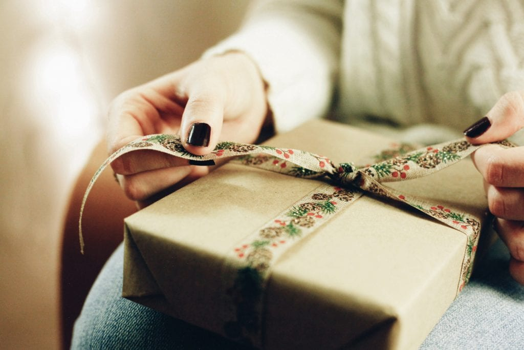 Close-up of a person opening a present wrapped in brown paper and holiday ribbon