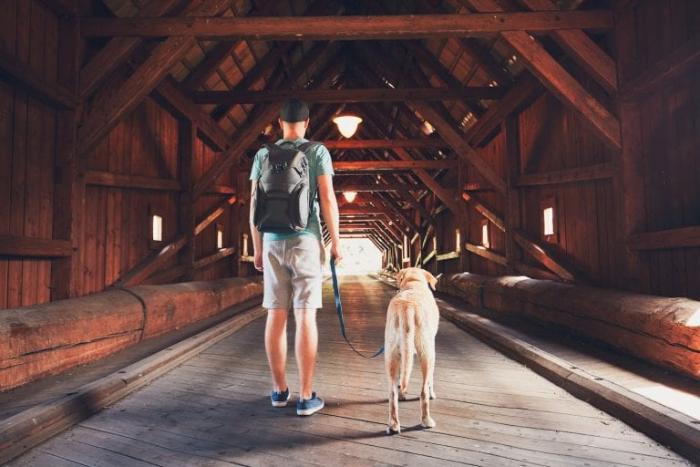 A man and his dog walk down a wooden covered bridge
